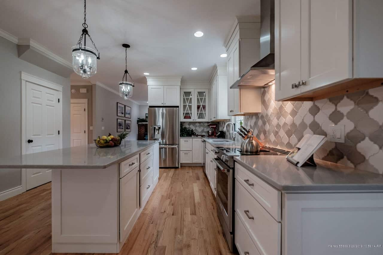 Large new L-shaped kitchen with white cabinets, hardwood floor and recessed lighting in a colonial house.