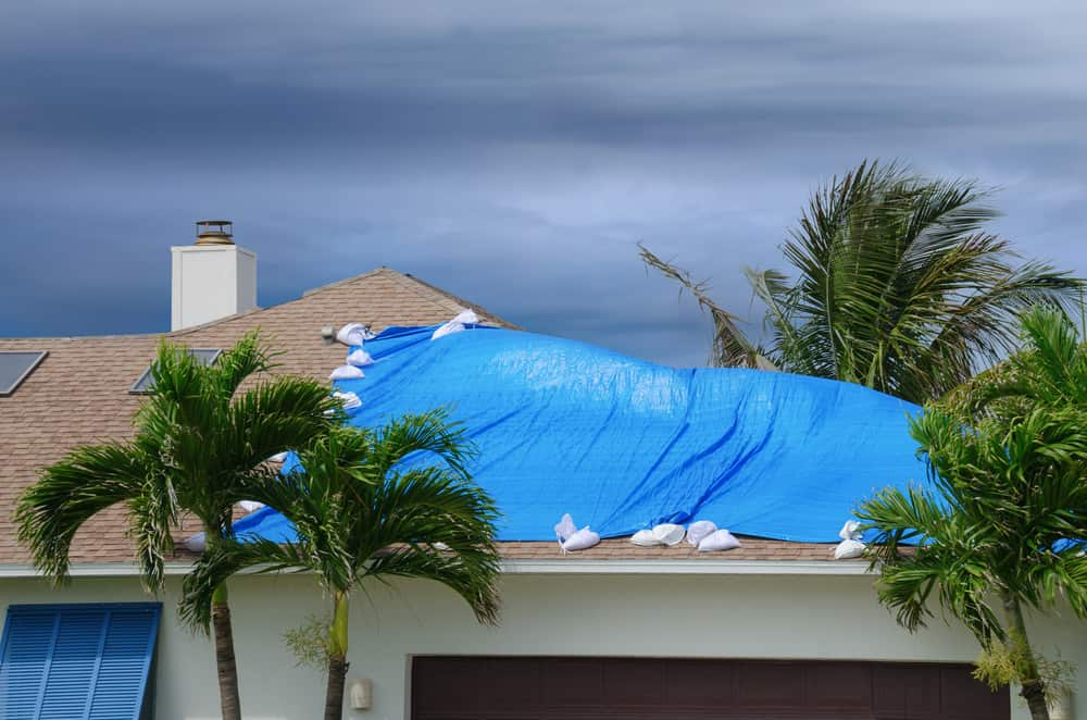 Photo of a damaged roof with tarp