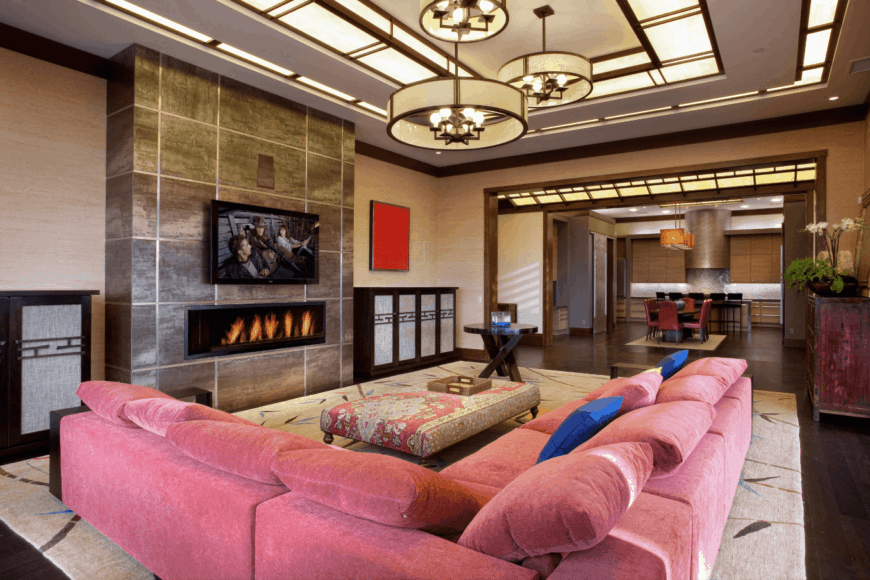 Cozy living room boasts a pink L-shaped sectional lighted by lovely drum chandeliers that hung from a frosted glass paneled ceiling. It has a modern fireplace fixed in an accent wall that will keep you warm and comfy.