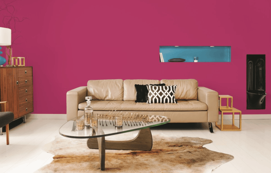 Classic living room showcases a magenta wall with blue inset. It has a cream leather sofa facing a glass top coffee table that sits on an irregular shaped rug.