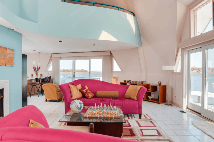 An airy living room with white tiled flooring and suspended ceiling. It includes pink sofas on a square patterned velvet rug.