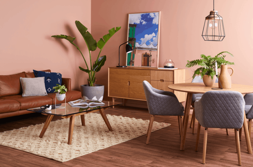 Salmon pink living room features a light wood console table and brown sectional paired with glass top coffee table. It is accented with potted plants that add life to the space.