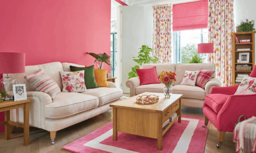 Wooden coffee table surrounded with couches and sits on a velvet rug in this pink living room. It includes indoor plants that create a tropical ambiance.