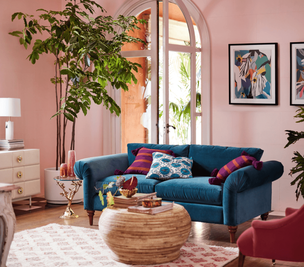 Light pink living room features a vibrant blue wing sofa paired with a round center table. It has a huge indoor plant that adds freshness to the area.