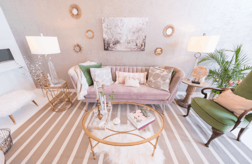 Fabulous living room with rose gold accents. It is designed with small sunburst mirrors and a wall art piece mounted on the blush pink wall.