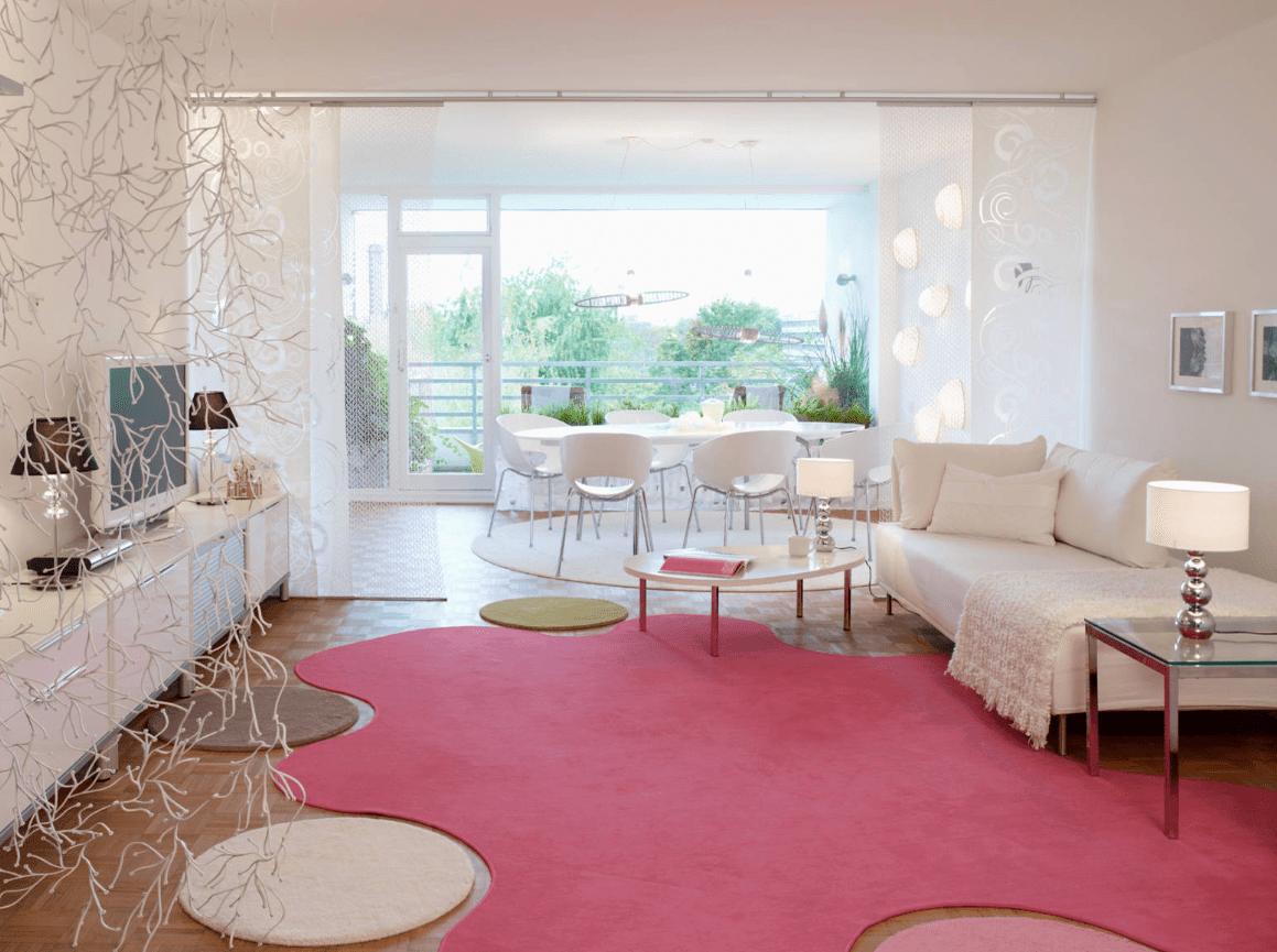 Peaceful white living room accented with a gorgeous pink rug features a white sofa that doubles as bed. It is an open area where you can see the dining and the balcony instantly.