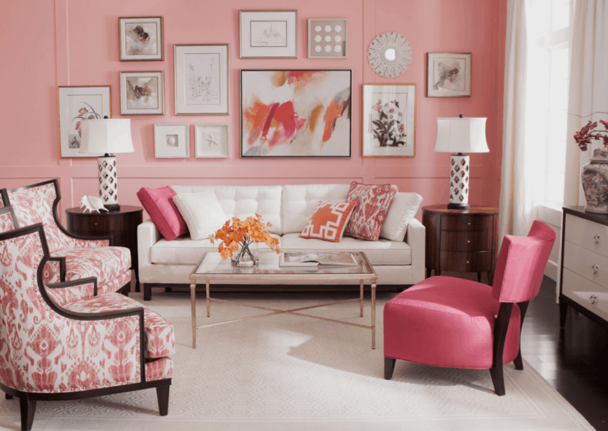 Light pink living room designed with gallery frames mounted above a tufted white loveseat. It has dark hardwood flooring topped with a white textured rug.