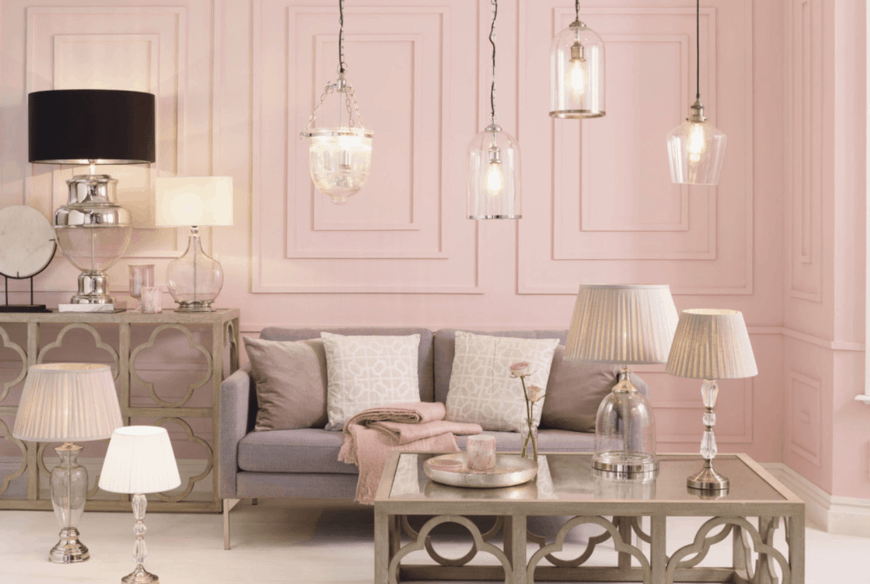 A sweet pink living room lined with glass pendant lights that hung over a gray couch paired with ornate wood coffee table. Various styled table lamps are all over the room.