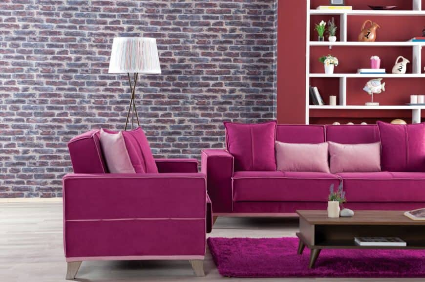 This living room boasts an accent brick wall with magenta sofas that complements the rug underneath a wooden coffee table.