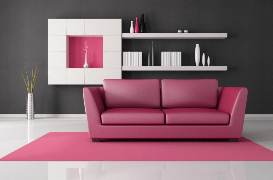 Sleek living room with a pink couch and rug over glossy white floor. It includes white floating shelves mounted on the gray wall.