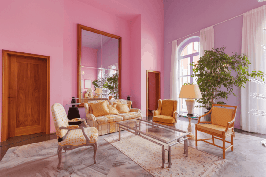 Charming living room with pink and purple walls. It has arched windows covered with sheer curtains.