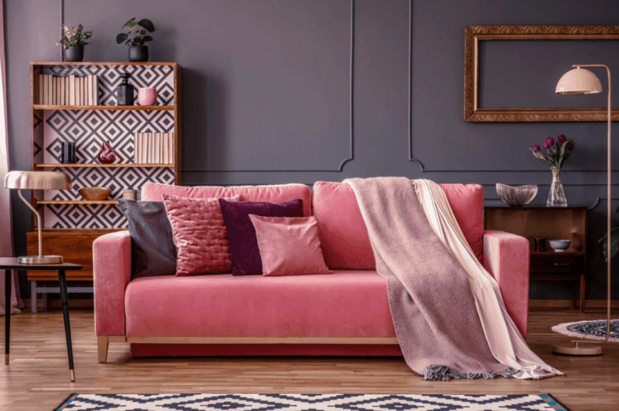 A pink velvet sofa with pillows and throw blankets brightens up this gray living room.