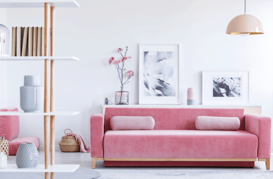 White living room accented with a pink sofa and floor chair. It is decorated with wall frames and a sakura flower.