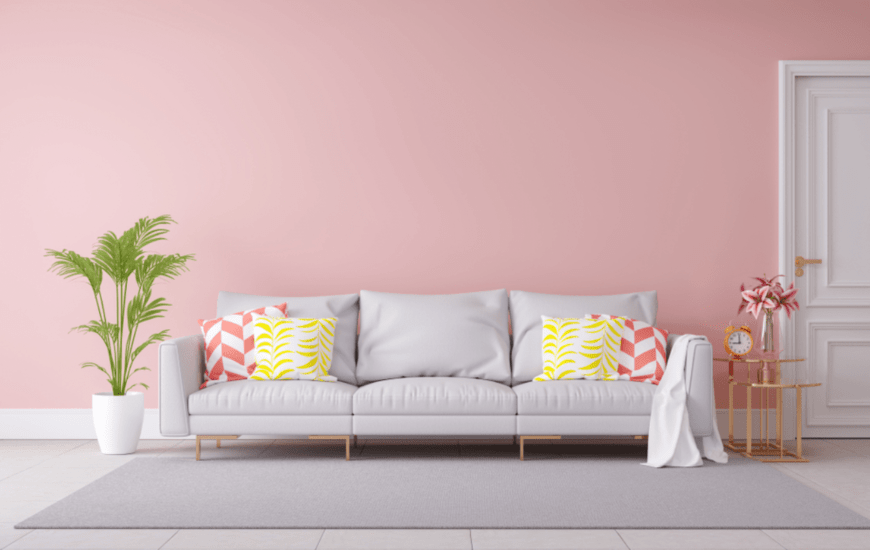 A gray sectional with a wooden side table and potted plant lays on the pastel pink wall. This living room has white tiled flooring topped with a gray rug.