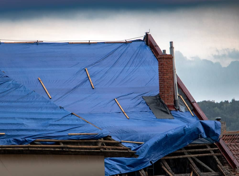 A tarp protecting a damaged roof during a storm.