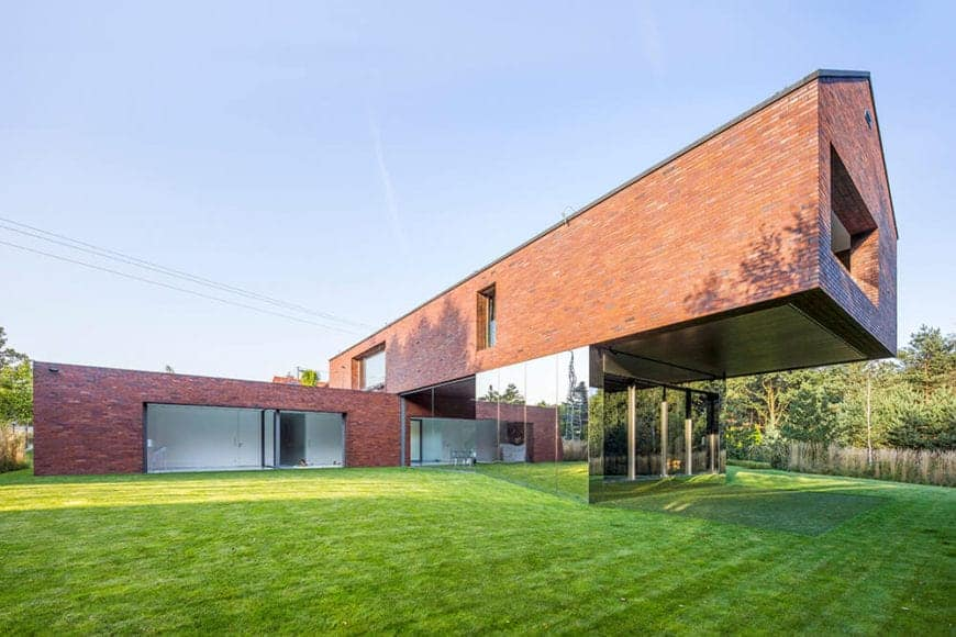 Huge contemporary house features a fascinating mirrored architecture reflecting the expansive lawn and providing an illusion of larger space. The rest of the walls is built with bricks and glass windows.