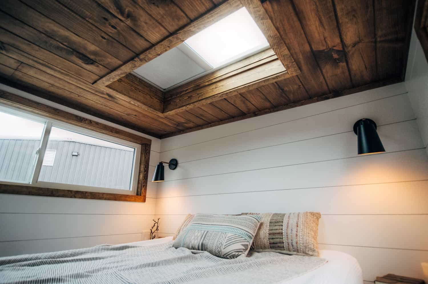 Rustic bedroom loft in a tiny home with skylight