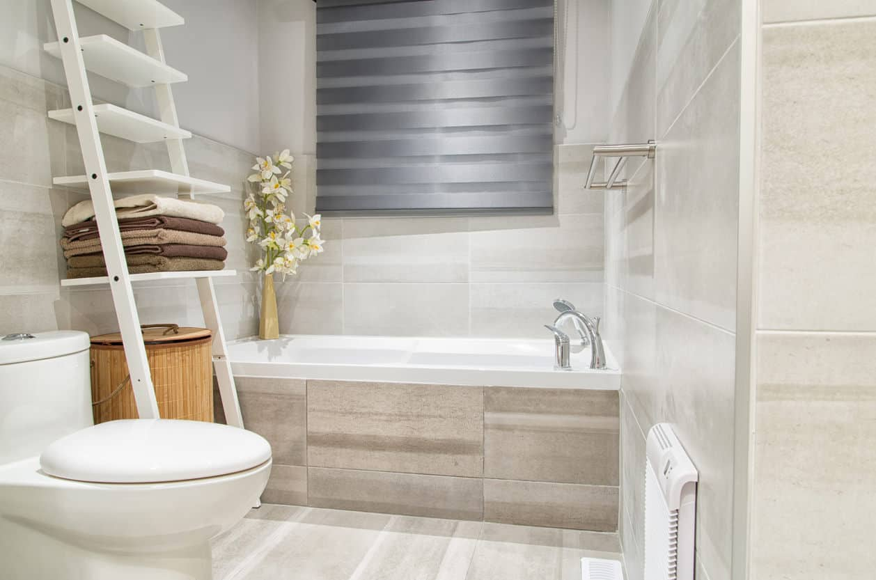 This is an example of a nicely design, yet modest and small primary bathroom with an alcove tub. The side of the alcove is a tan tile that looks like wood which is slightly darker than the other off-white tile in the rest of the bathroom.