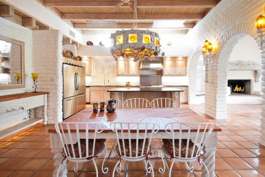 Gorgeous kitchen features white brick walls and arches along with exposed wood beams ceiling. It is lighted by a unique drum chandelier and matching wall sconces.