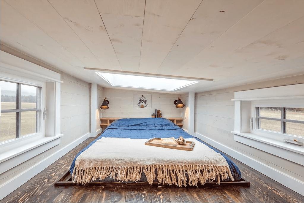 Spacious bright tiny house loft with a skylight and windows