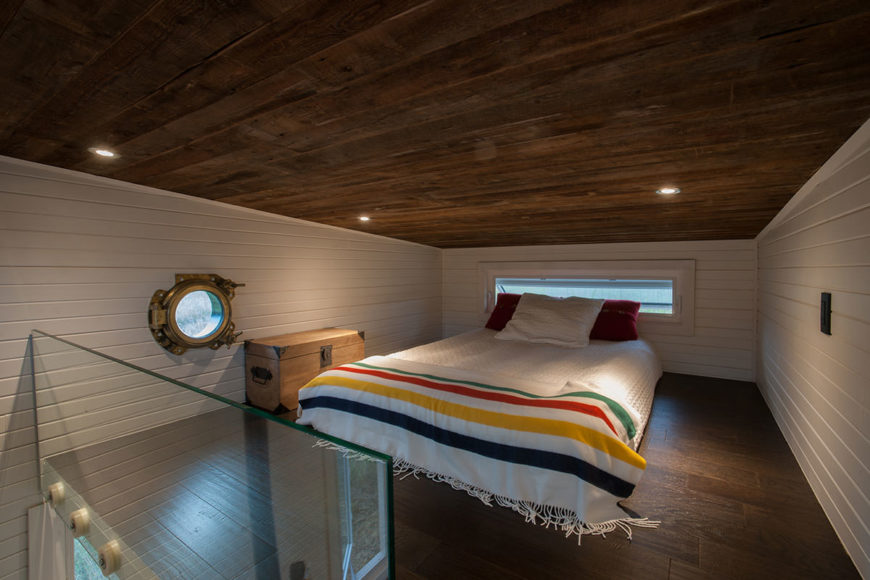 Spacious white-walled loft bedroom with dark wood ceiling and flooring