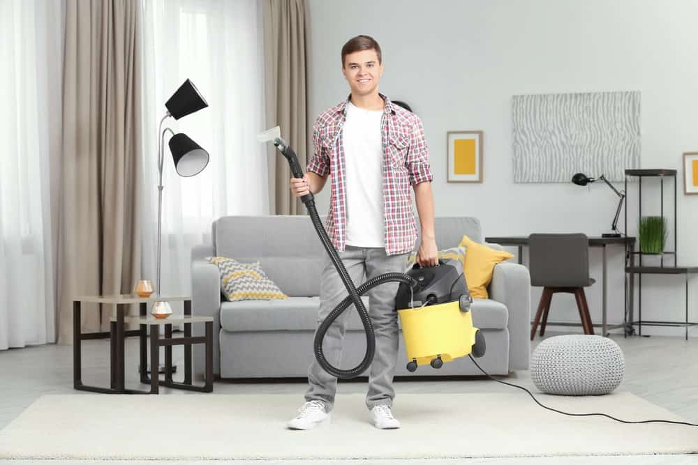 Young man holding a garment steam cleaner in the living room.