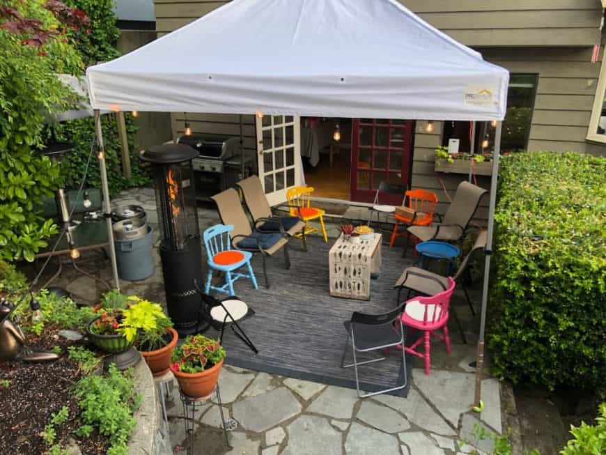 View of party patio with chairs, lights and tent canopy