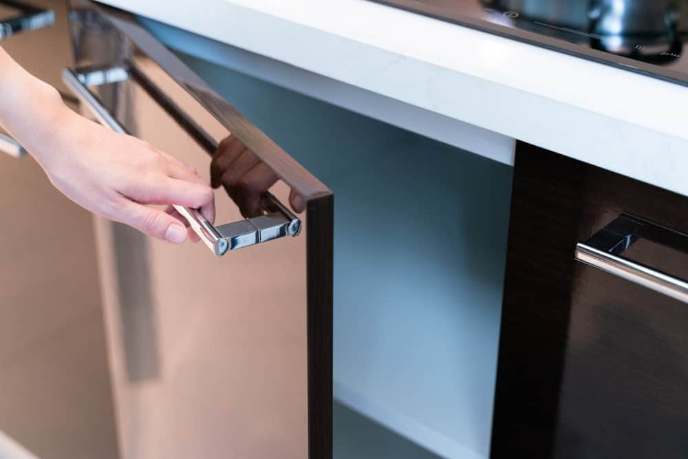 Hand pulling a slab style kitchen cabinet door.