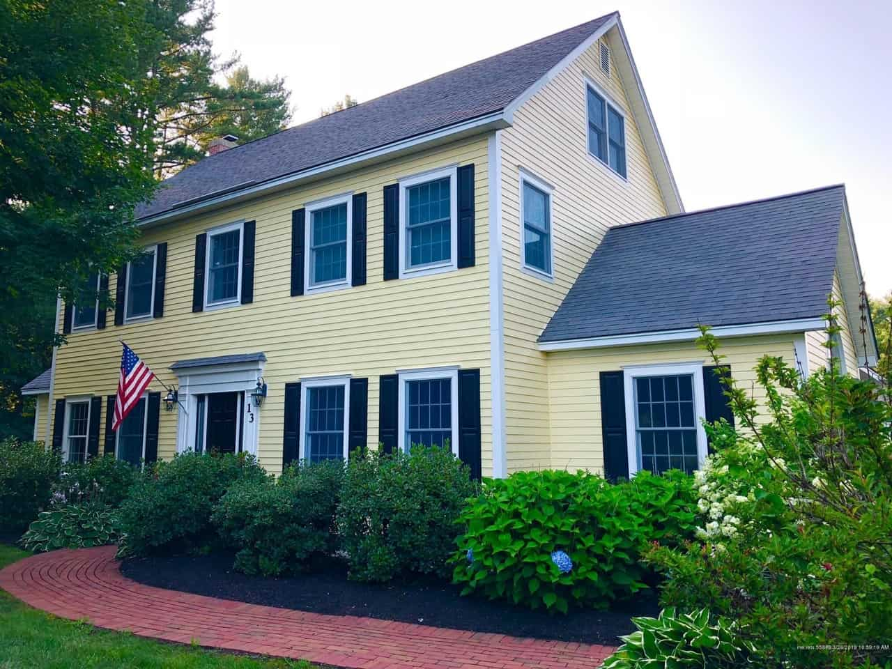 Yellow colonial house with black shutters and white trim