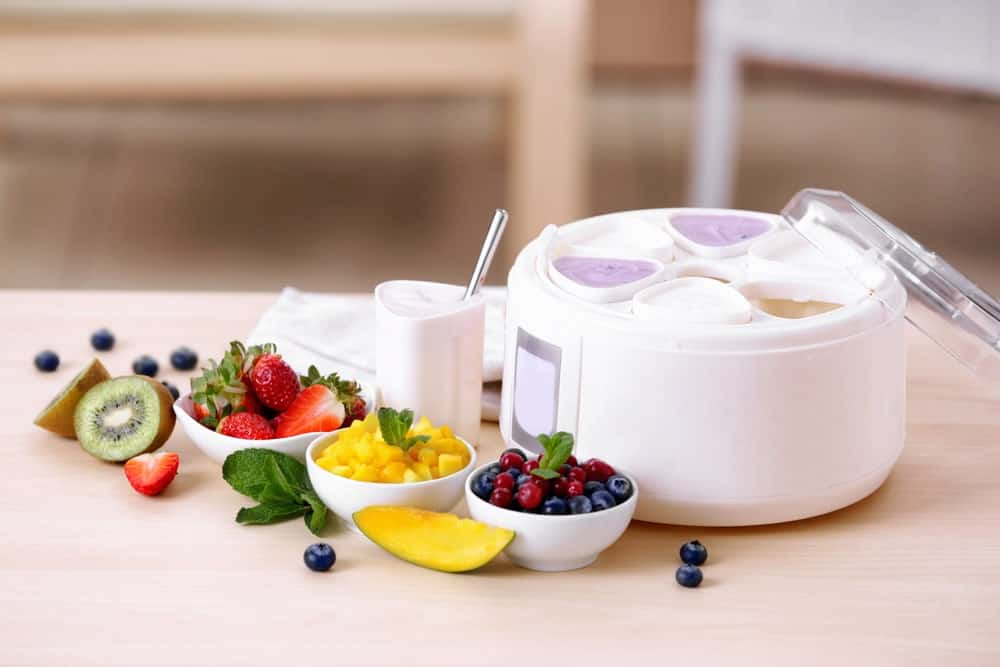 Ingredients and a yogurt maker on a table.