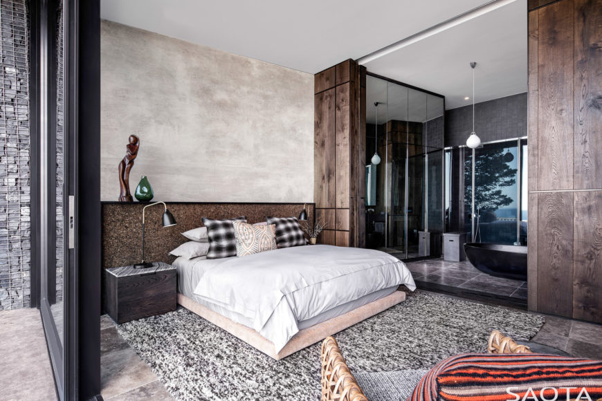 Contemporary primary bedroom features a low bed that sits on a gray rug over a stone tiled flooring. It has a dark wood nightstand with desk lamp.