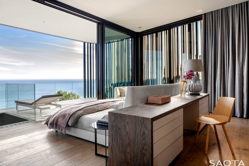 Primary bedroom with a stunning beachfront view. A dark wooden desk paired with natural tone wood chair is situated at the back of the bed's headboard.