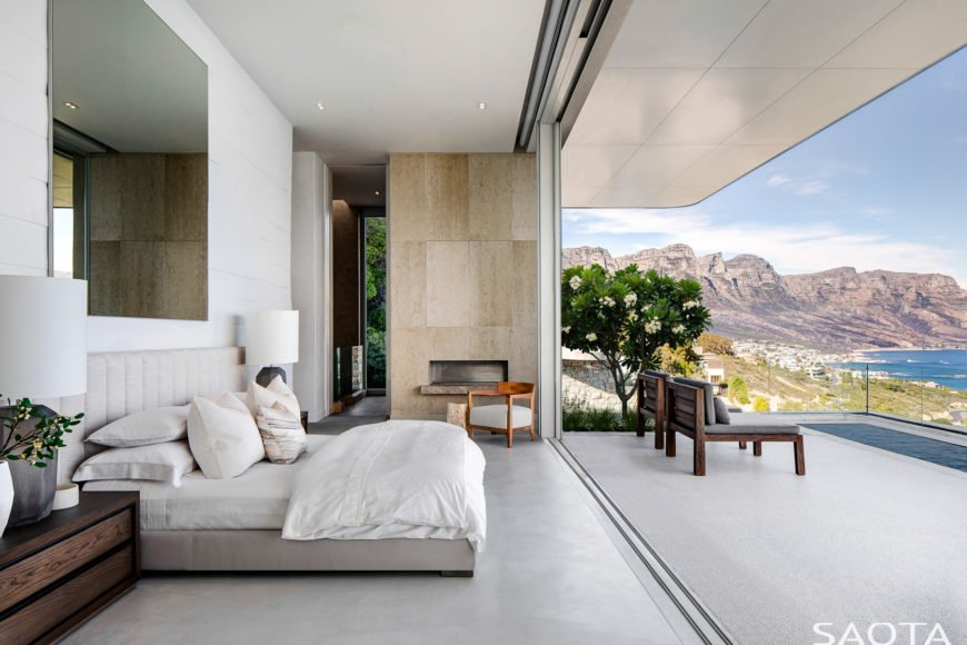 Magnificent primary bedroom showcases a glass wall that overlooks a spectacular scenic view. It has a tufted bed over concrete flooring.