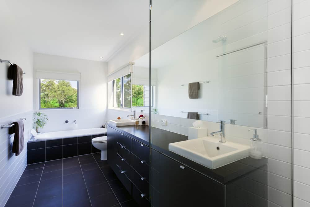 Here's a long rectangle-shaped primary bath with black floor tile that rises up the side of the alcove tub and matches the black double-sink vanity. The black tile contrasts very nicely with the white grout, white walls and white ceiling.