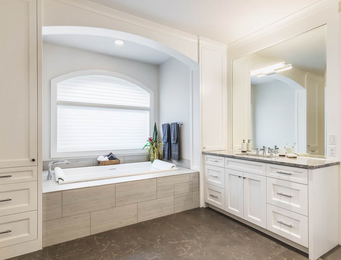 Photo example of a modern bathtub alcove with a slightly arched supporting beam. The alcove is light via large arched window and recessed light. The rectangle-shaped tub is large enough to accommodate most adults and blends in well with the white, off-white and tan <a class=