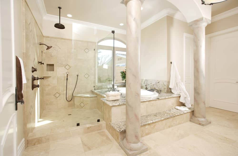 Check this Roman-style primary bathroom with columns flanking a raised alcove soaking tub which also opens up into a huge open shower area. There's an arched window next to the tub as well as recessed lighting providing plenty of light in this extraordinarily luxurious primary bath.