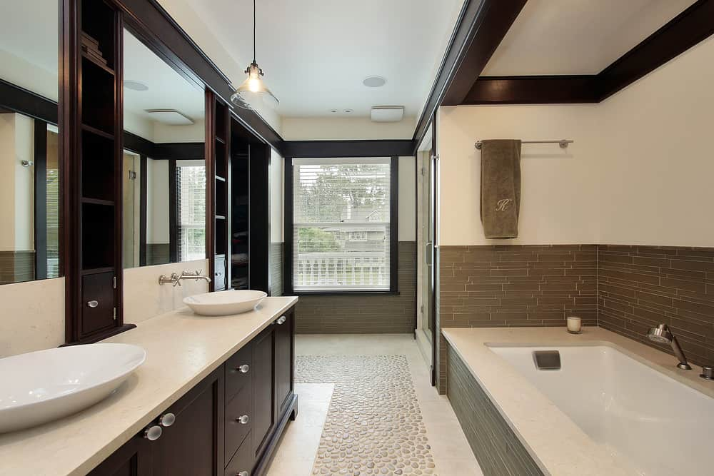 The alcove here is opposite the contemporary vanity with vessel basins. The alcove has brown tile rising up half-way the wall. The ceiling includes dark wood beams that match the dark vanity wood and window trim.