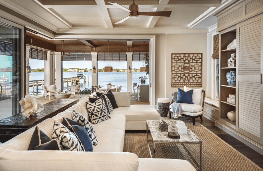 The off-white large U-shaped sectional sofa dominates the living room. It matches with the coffered ceiling that has a ceiling fan in the middle hanging over the modern coffee table over the woven wicker area rug that suits the dark hardwood flooring.