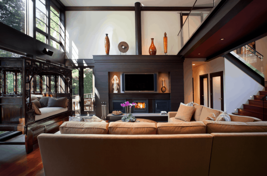 This charming and cozy living room has a high white ceiling separated from the white walls by dark wooden molding that blends in with the large wooden structure that houses the TV over the fireplace adorned with oriental decors that gives a nice background for the large L-shaped beige sofa.