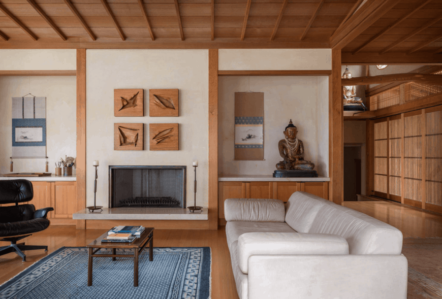 This is a warm and cozy living room that is dominated by the wooden elements in the wooden ceiling, hardwood flooring and the walls that are adorned with wooden moldings and cabinets bearing oriental and Buddhist decors flanking the fireplace.
