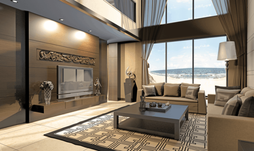 The high beige walls of this elegant living room is dominated by tall windows that maximize the vertical space and amps the natural light shining on the patterned area rug and the gray sofas facing the TV on a dark wooden wall with oriental decors and carving.