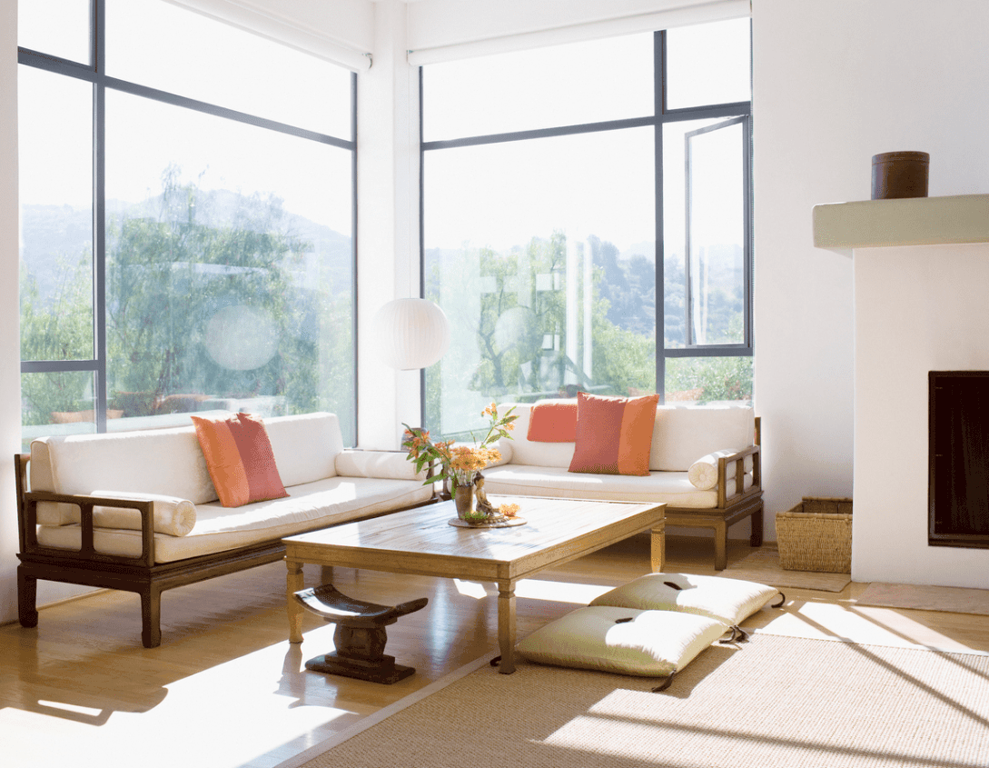 The tall windows dominating the corner brightens the pair of white-cushioned sofas with wooden frames paired with a wooden coffee table that suits the light hardwood flooring topped with a wooden beige area rug by the fireplace that blends in with the white walls.