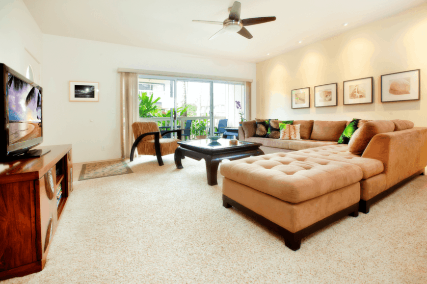 This cozy living room is dominated by a large beige L-shaped sectional velvet sofa that complements the beige carpeted flooring and the light pink walls adorned with framed artworks with brown frames matching the coffee table.