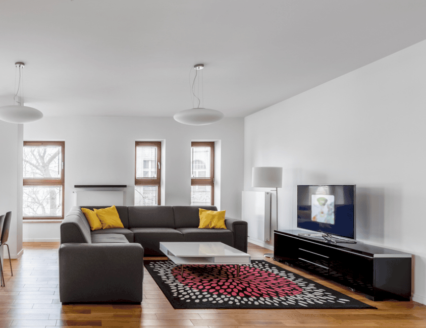 The white walls, ceiling and pendant lights of this comfortable living room is contrasted by the dark gray L-shaped sectional sofa, black area rug with pink and white patterns as well as the sleek black entertainment table that supports the TV.