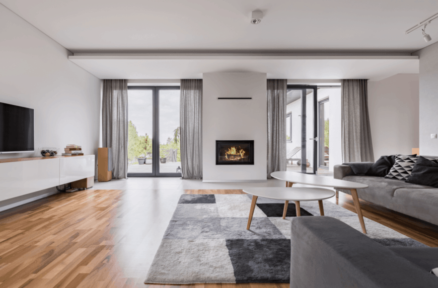 This spacious living room has a bright demeanor due to the pair of glass doors flanking the fireplace that is embedded into the white wall. This is complemented by the hardwood flooring that is topped with a gray patterned area rug that is well matched to the gray velvet sofas.