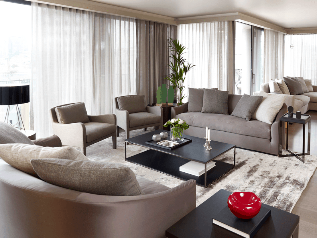 This lovely living room is surrounded by curtained sliding glass doors and windows that bring in an ample supply of natural lights to the gray sofas and cushioned armchairs surrounding the rectangular black coffee table that stands out against the white and gray area rug.