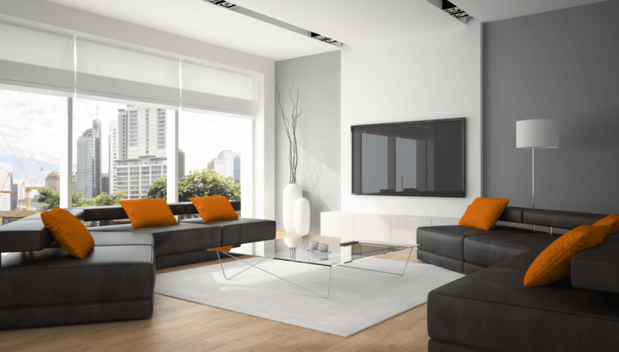 The deep orange throw pillows stand out against the two black sectional sofas flanking the modern glass-top coffee table over a light gray area rug that complements the light hardwood flooring and the white ceiling augmented by the large floor-to-ceiling windows.