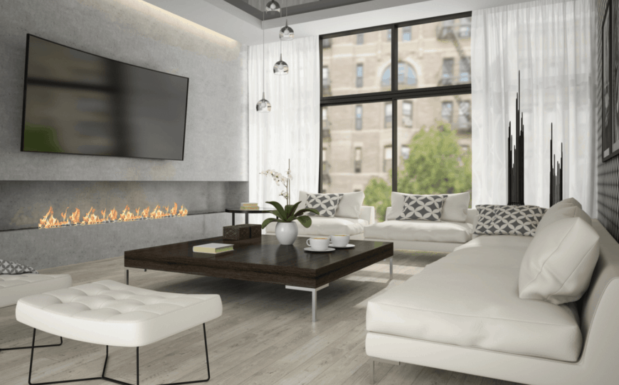 This predominantly gray living room has a modern fireplace dominating the lower half of the wall that supports a massive TV facing the large wooden coffee table surrounded by a white leather sofa set that complements the light hardwood flooring.