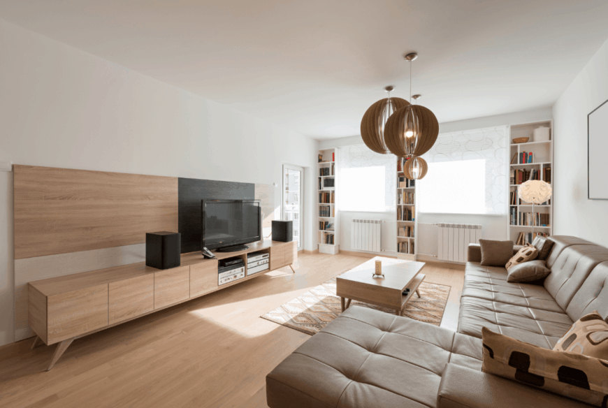 The spherical brown pendant lights hanging over the wooden coffee table is a nice accent to the light hardwood flooring that is complemented by the large L-shaped leather sofa facing the wooden entertainment cabinet bearing the TV.