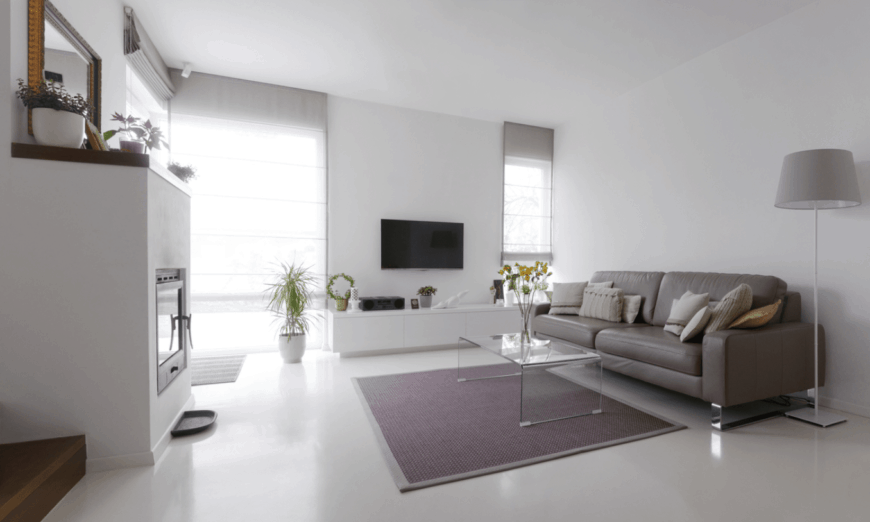 The white fireplace has a thick mantle with a wooden top for small potted plants and a brass-framed mirror that stands out against the white wall that blends with the white flooring. This is contrasted by the gray leather sofa and its area rug bearing a modern glass coffee table.